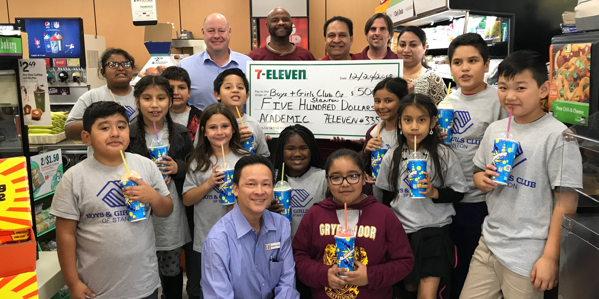 Group of students at 7-eleven holding a large $500 dollar check